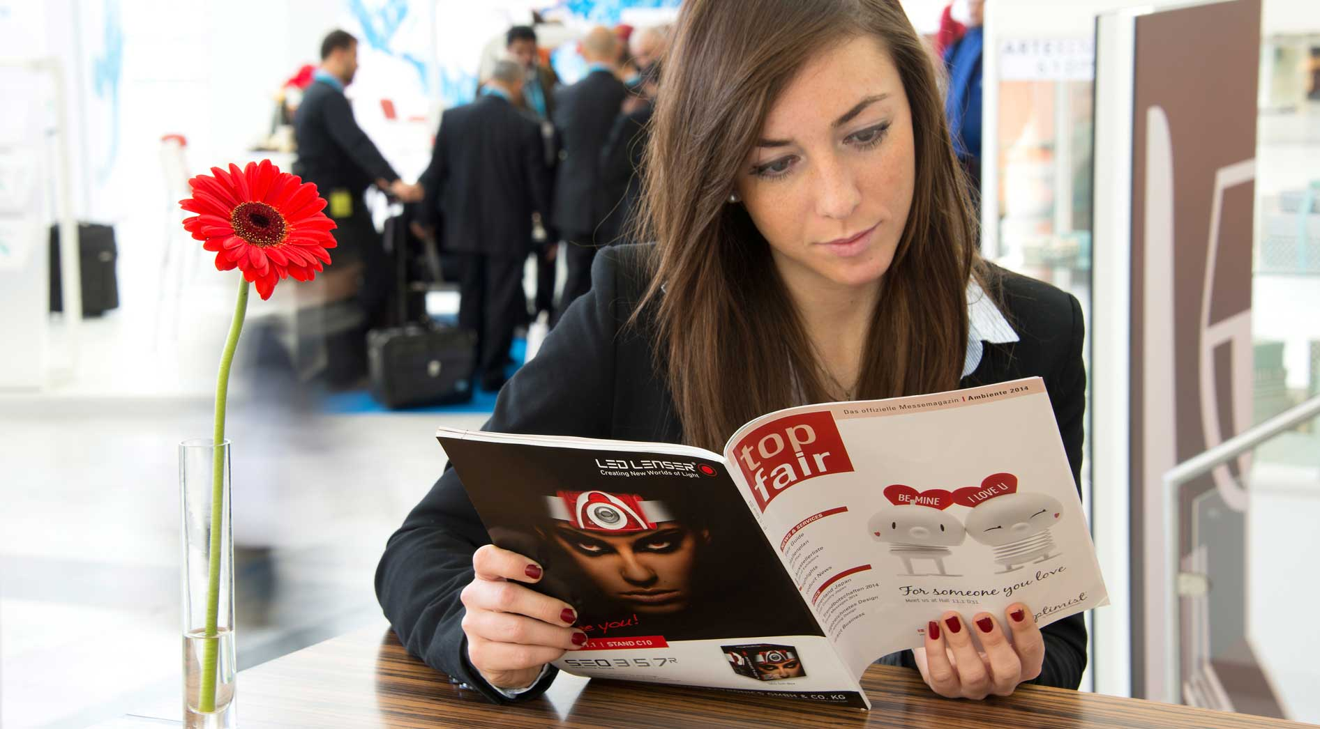 Woman is reading the trade fair magazine top fair